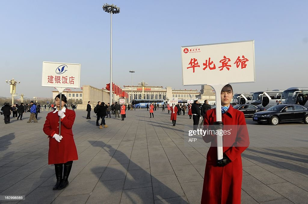 Hotel guides hold billboards as they wait for delegates after the opening session of the Chinese People's Political Consultative Conference (CPPCC) at the Tiananmen square in Beijing on March 3, 2013. Thousands of delegates from across China meet this week to seal a power transfer to new leaders whose first months running the Communist Party have pumped up expectations with a deluge of propaganda.