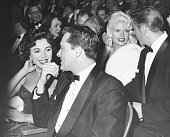 Hotel heir Nicky Hilton and actress Joan Collins sitting together at a the premiere of the film 'Heaven Knows Mr Allison' with Jayne Mansfield and...