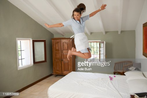 Hotel maid jumping on bed in room