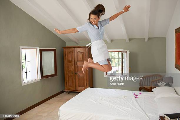 Hotel criada saltar na cama na sala