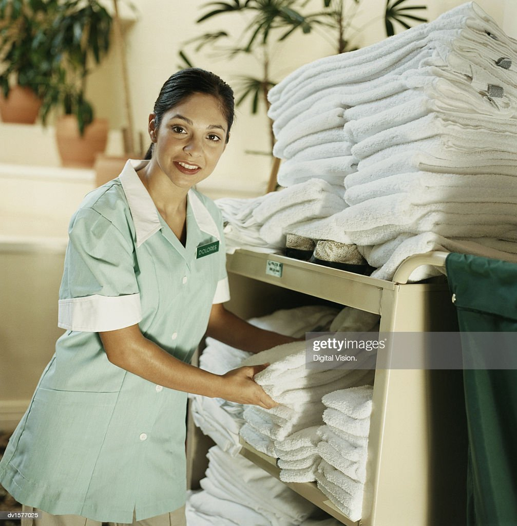 Hotel Maid Sorts Through Towels in a Laundry Basket