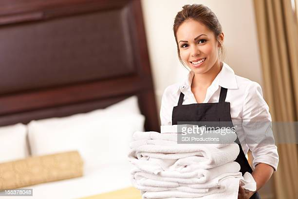 Hotel maid with towels in guest room