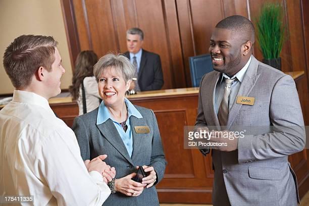 Hotel management parler de quelque chose avec les clients dans le hall