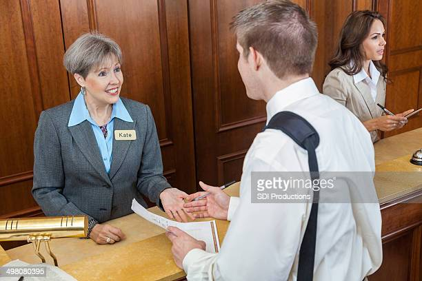 Hotel manager assisting guest with bill as he checks out