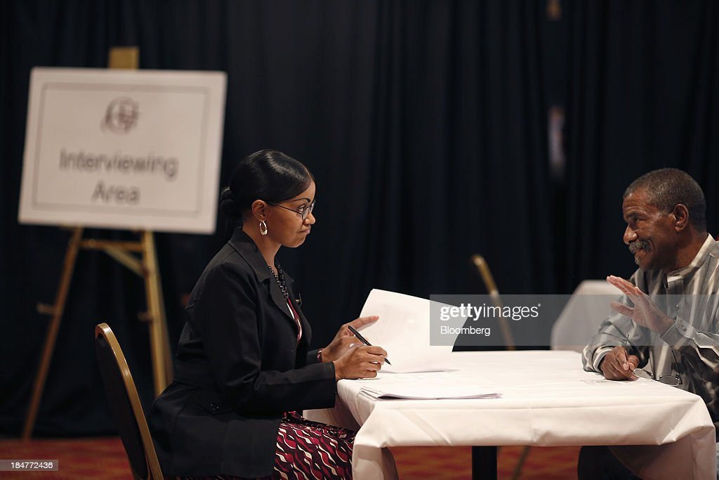 A hotel manager, left, conducts an interview with a job seeker during a job fair hosted by the Galt House Hotel in Louisville, Kentucky, U.S., on Monday, Oct. 14, 2013. Improvement in the U.S. labor market may soon speed up, building on gains during the past year, Federal Reserve researchers said, citing six employment indicators. Photographer: Luke Sharrett/Bloomberg via Getty Images