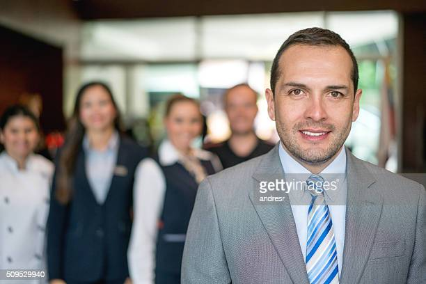 Hotel manager with staff at the background