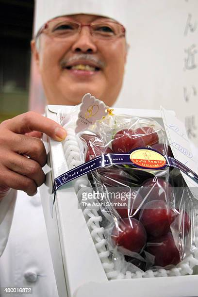 Hotel Nikko Kanazawa executive chef Masayuki Hirai displays a box of 'Ruby Roman' grapes after the first auction of the season at Kanazawa central...
