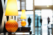 Reception area in luxury hotel or office close up on lamp with people traveling in and out the front entrance
