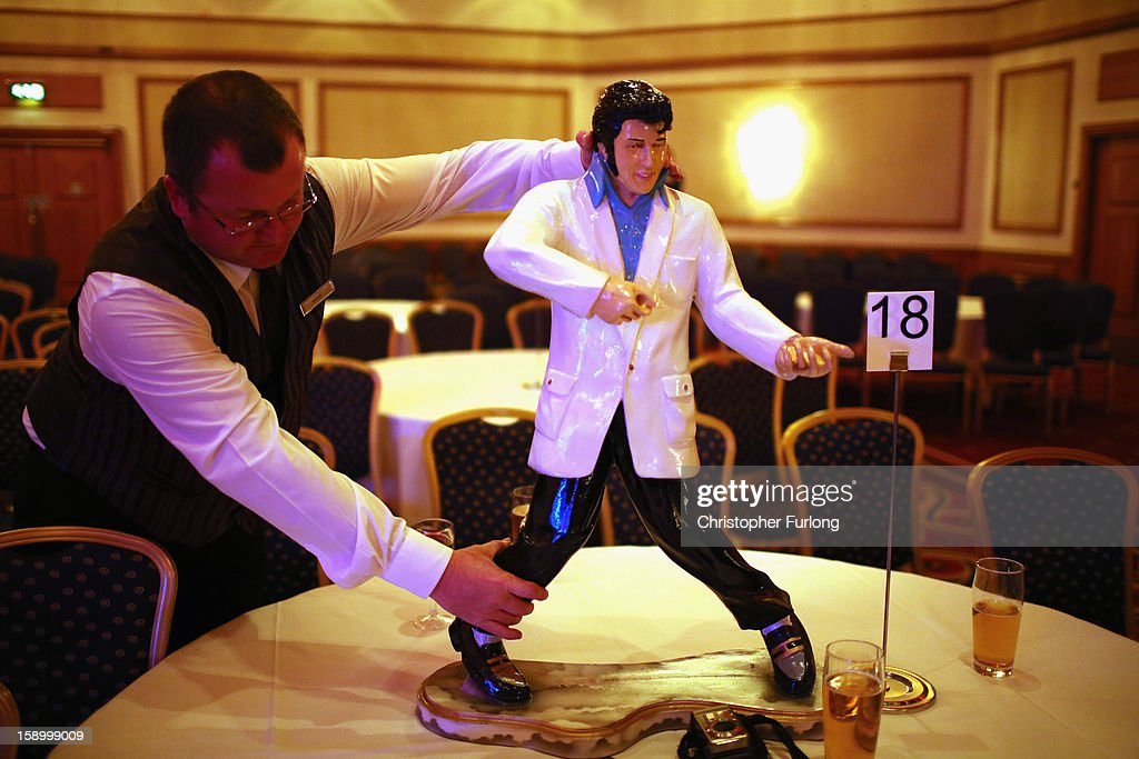 A hotel porter arranges an Elvis statue during the European Elvis Championships at the Hilton Hotel on January 4, 2013 in Birmingham, England. Elvis impersonators are taking part in three days of competition from which a winner will go forward to the International Elvis Tribute Artist Contest in Memphis, USA.