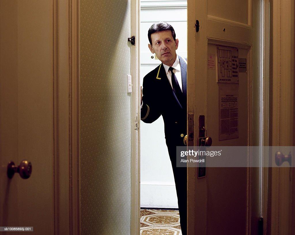 Hotel porter looking around door : Stock Photo