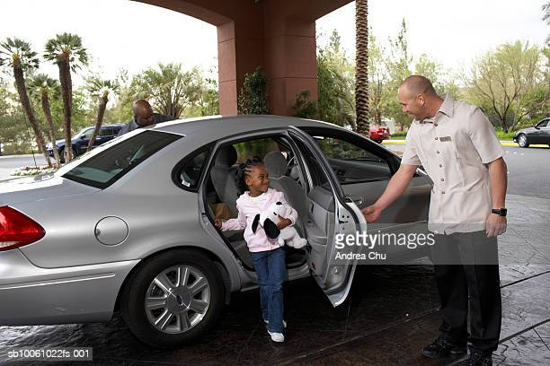 Hotel porter opening car door for girl (4-5 years)