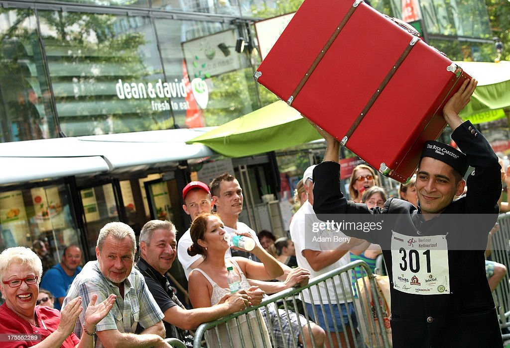 A hotel porter runs with a suitcase during the Waiters' Derby (Kellner Derby in German) on August 4, 2013 in Berlin, Germany. At the annual event, brought back into existence in 2011 on the 125th anniversary of the Kurfuerstendamm (known locally as the Ku'damm), a main shopping thoroughfare, waiters, porters, cooks and bartenders run a 400-meter track while performing their regular occupational duties. The event was reinstated after a hiatus since the 1950s, when it was created to bring a sense of normal life back to Berlin after World War II under the Allies, a period in which gastronomical interest in the isolated Western part of the city suffered.