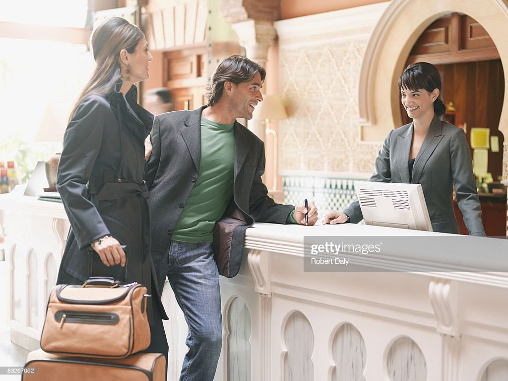 Hotel receptionist checking couple in : Stock Photo