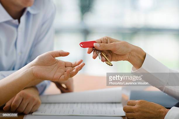 Hotel receptionist handing room key to guest