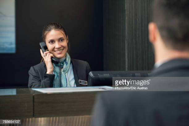 Hotel receptionist talking on phone
