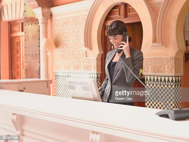 Hotel receptionist talking on telephone