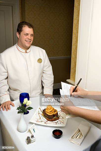Hotel room service attendant with tray of food and guest's hands signing bill