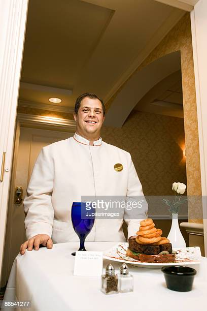 Hotel room service attendant with tray of food in hallway