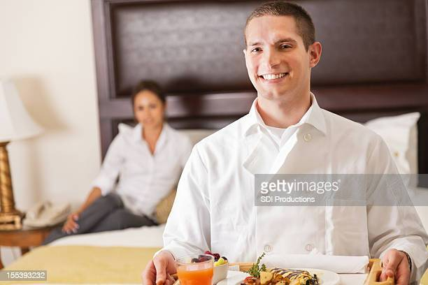 Hotel room service delivery man holding tray of breakfast