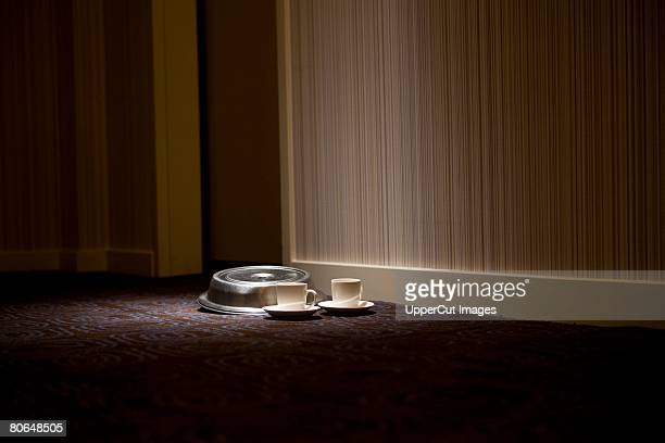 Hotel room service dishes on floor