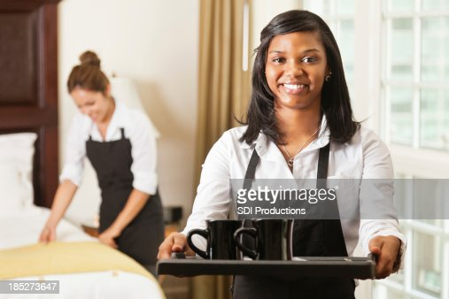 Hotel room service lady offering coffee on tray