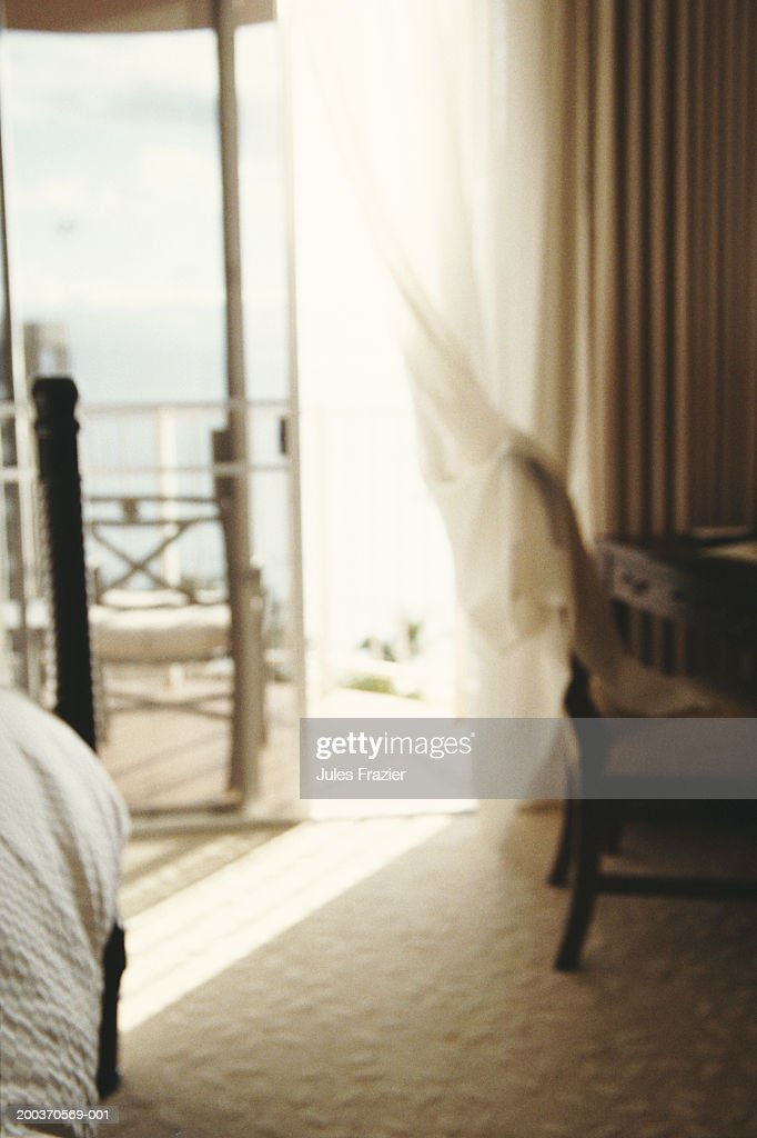 Hotel room with sliding glass door open onto balcony (defocused) : Stock Photo