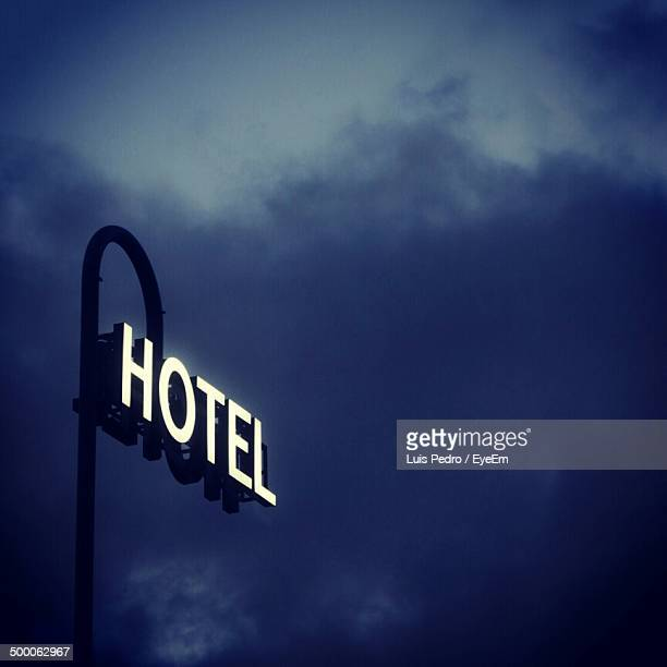 Hotel sign against cloudy sky at night