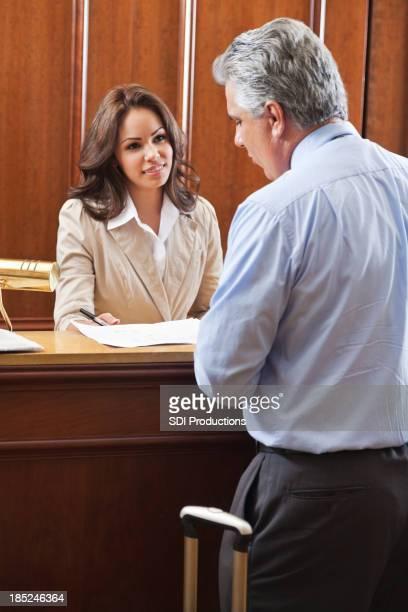 Hotelpersonal hilft Geschäftsmann check-out