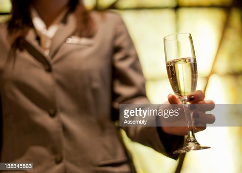 Hotel staff member offers a glass of champagne : Stock Photo