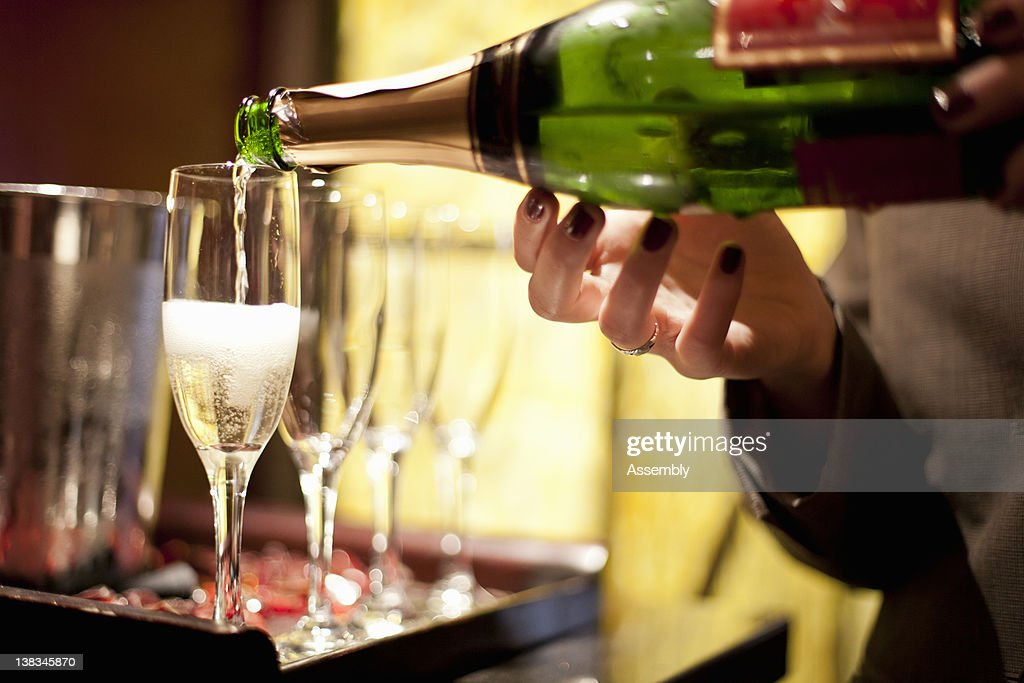 Hotel staff member pours champagne into glasses : Stock Photo