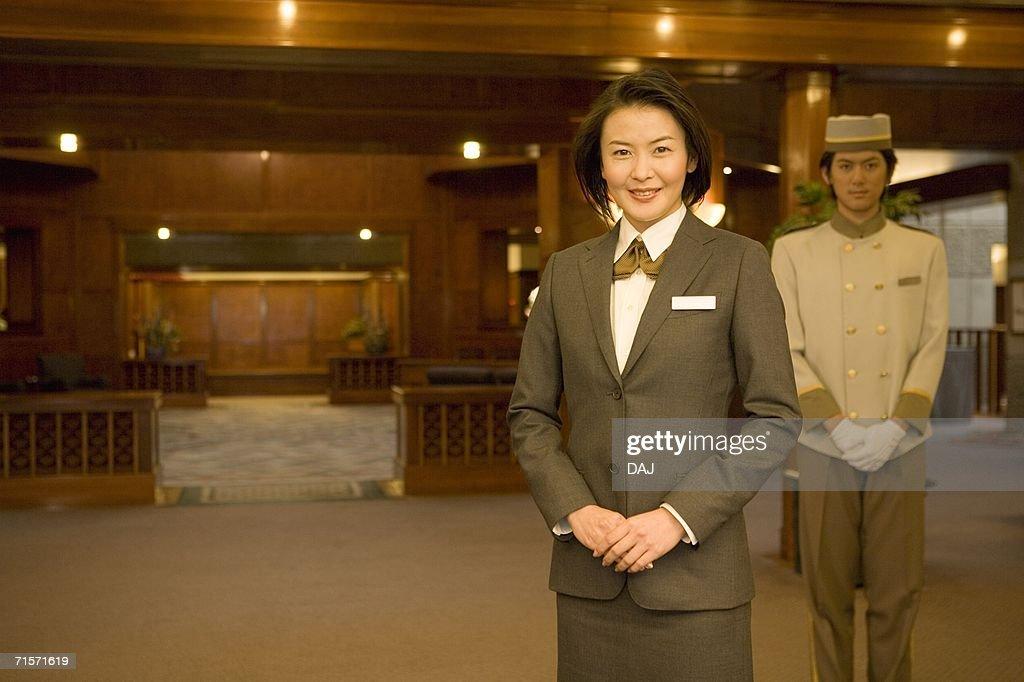 Hotel staffs, reception desk in background, smiling, portrait, front view