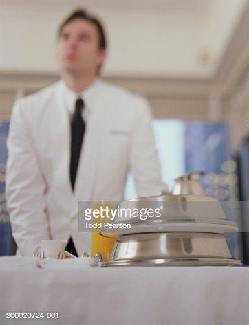 Hotel waiter pushing room service cart stock photo getty for Hotel room service cart
