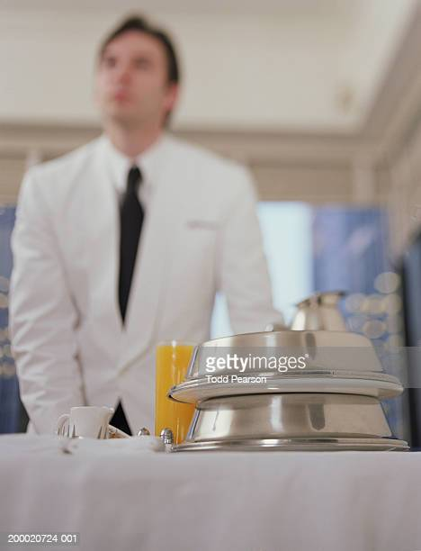Hotel waiter pushing room service cart (selective focus)