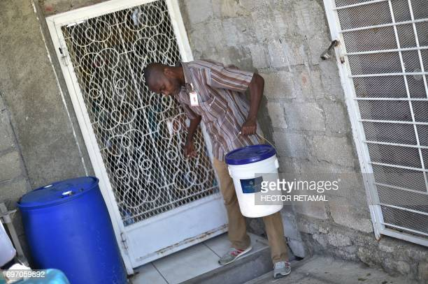 A hotel worker carries a bucket with used soap at a hotel in PortauPrince on June 6 2017 A Haitian program to recycle used soap bars from luxury...