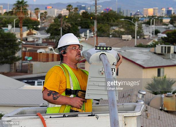 Hotelcasinos on the Las Vegas Strip are seen behind city of Las Vegas field electrician John Meier as he checks the level of a new LED fixture while...