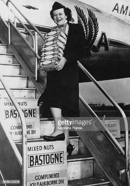 Hotesse de l'air americaine les bras charges de paquets de noix qui seront largues au dessus de la ville par la 101 eme division de parachutistes en...