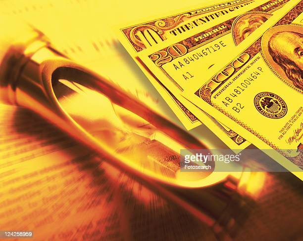Hourglass and US banknotes on newspaper, blurred motion, toned image, high angle view