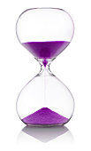 Hourglass with violet sand measuring time against white background