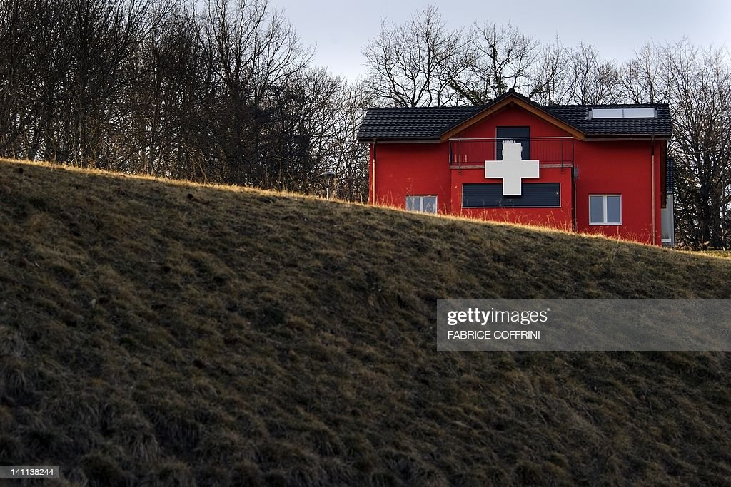A house adorned with a white cross, like the Swiss flag, is seen on March 11, 2012 in Moudon. Swiss citizens accepted a referendum on Federal level to limit the construction of second homes in communes to 20 percent. The environmental organisation that brought the initiative argued the construction boom in mountain resorts had led to a waste of natural resources and massively boosted property prices, disadvantaging the local population.