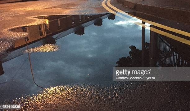 House Along With Cloudy Sky Reflected In Puddle On Street At Night