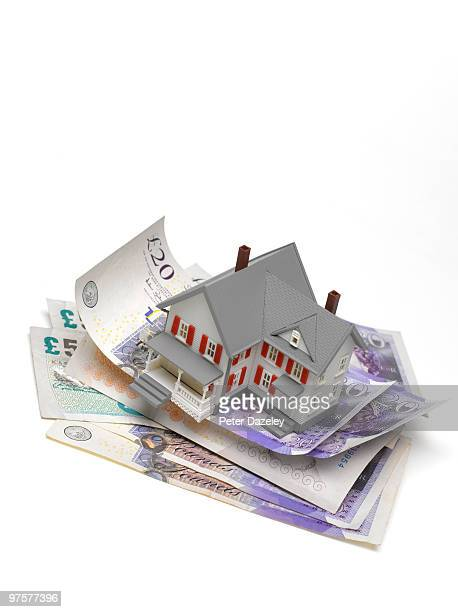 House balanced on stack of pound notes