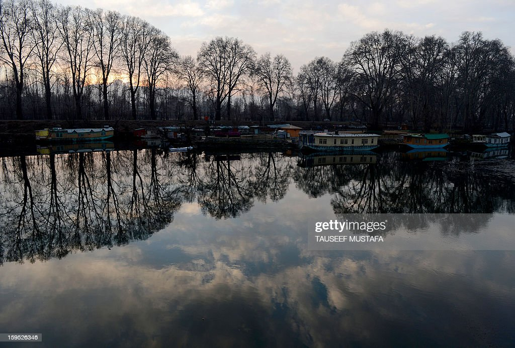 House boats are reflected at sunset on Dal Lake in Srinagar on January 15, 2013. Indian Prime Minister Manmohan Singh warned Tuesday that there 'cannot be business as usual' with neighbouring Pakistan after last week's deadly flare-up along the border in disputed Kashmir.The Indian government has accused Pakistani soldiers of crossing into Indian territory and killing two of its soldiers on January 8. AFP PHOTO/Tauseef MUSTAFA