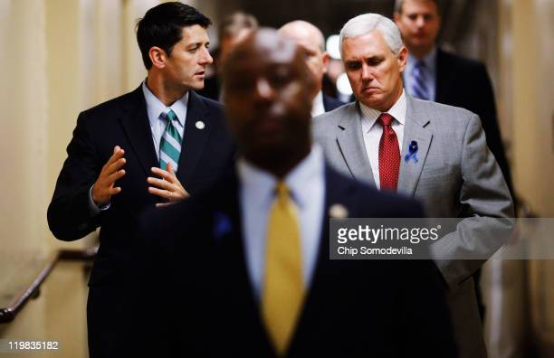 House Budget Committee Chairman Paul Ryan talks with US Rep Mike Pence as they head to a Republican conference meeting in the basement of the US...