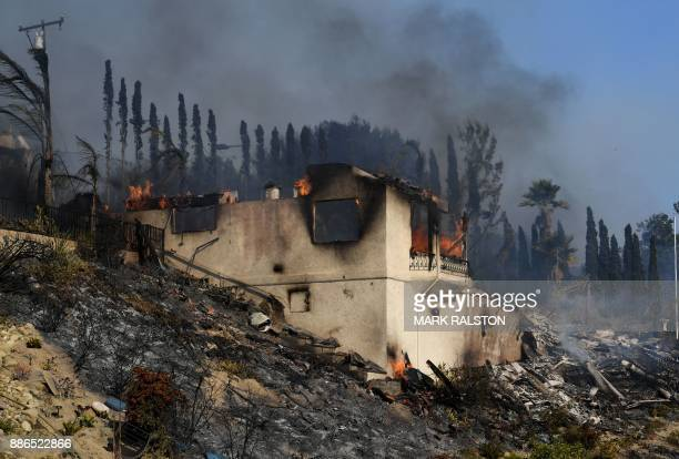 A house burns during the Thomas wildfire in Ventura California on December 5 2017 Firefighters battled a windwhipped brush fire in southern...