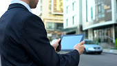 House buyer browsing housing offers on tablet, waiting for realtor, technologies