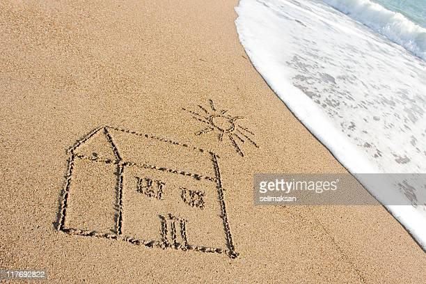 Maison dessin sur le sable de la plage de vagues de la mer