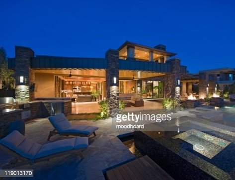 House exterior lit up at night, with patio furniture : Foto de stock
