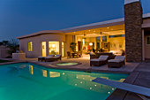 House exterior with sunloungers on patio by swimming pool