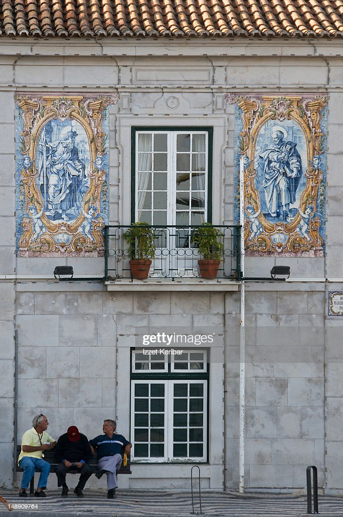 House facade in Cascais decorated with tiles with men chatting in front. : Stock Photo