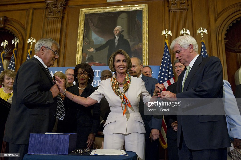 House Financial Services Chairman Barney Frank, D-Mass., and Senate Banking Chairman Christopher J. Dodd, D-Conn., each receives pens from House Speaker <a gi-track='captionPersonalityLinkClicked' href=/galleries/search?phrase=Nancy+Pelosi&family=editorial&specificpeople=169883 ng-click='$event.stopPropagation()'>Nancy Pelosi</a>, D-Calif., after she signed the financial regulatory overhaul bill - which passed the Senate earlier today. The House passed the bill June 30. The bill moves to President Obama's desk for his signature before becoming law.